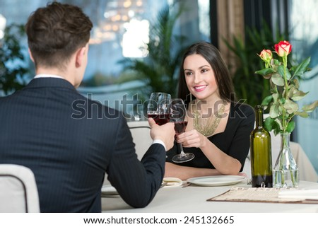 Portrait of beautiful girls sitting in restaurant together with her husband and drinking wine