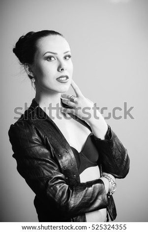 Portrait of beautiful glamorous woman in black leather jacket on light background