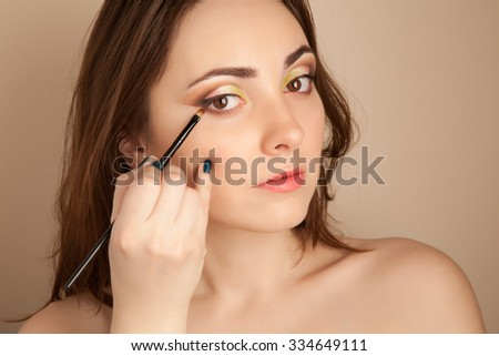Portrait of beautiful gorgeous woman doing her make-up - stock photo