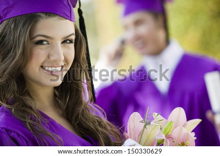Portrait of beautiful graduate student with flower bouquet - stock photo