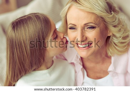 Portrait of beautiful granny smiling while her granddaughter kissing her - stock photo
