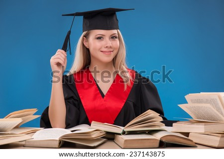 Portrait of beautiful happy blond girl in black cloak and master hat with many opened books smiling looking at camera