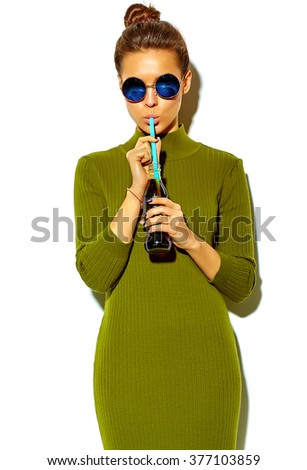 portrait of beautiful happy cute brunette woman girl in casual green hipster summer clothes with no makeup isolated on white in sunglasses drinking cola from bottle with straw - stock photo