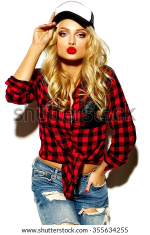 portrait of beautiful happy cute smiling blonde woman bad girl in casual red hipster winter checkered flannel shirt and blue jeans clothes with red lips and cap gives air kiss - stock photo