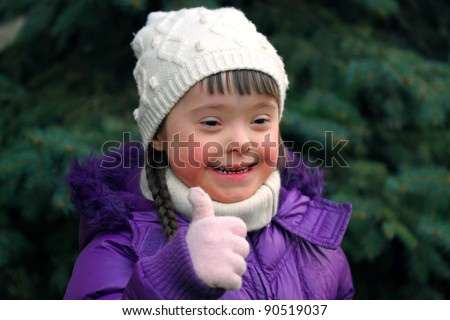 Portrait of beautiful happy girl giving thumbs up on background of the spruce - stock photo