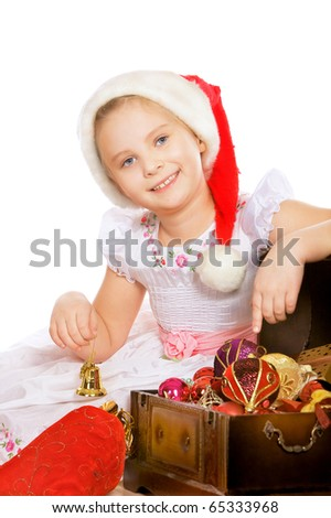 Portrait of beautiful happy girl in red cap with christmas toys