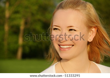 Portrait of beautiful happy laughing young woman in park, outdoor shot