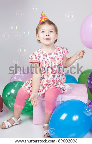 Portrait of beautiful happy little girl with balloons blowing bubbles in studio