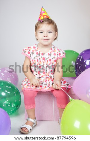 Portrait of beautiful happy little girl with balloons sitting on the big gift