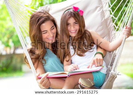 Portrait of beautiful happy mother with cute little daughter sitting on backyard in hammock and reading funny story, nice lovely family - stock photo