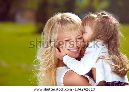 Portrait of beautiful happy mother with her daughter outdoors - stock photo