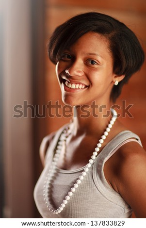 Portrait of beautiful happy smiling African American teenage girl. Closeup, shallow DOF, focus on eye. - stock photo