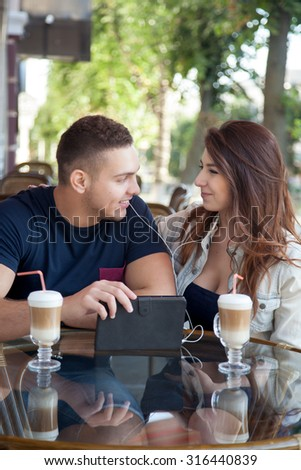 Portrait of beautiful happy smiling young adult couple in casual outfits sitting in street cafe sharing earphones, holding tablet and looking at the screen, glass of drink on the table