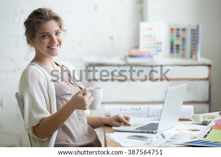 Portrait of beautiful happy smiling young designer woman sitting at home office desk with cup of coffee, posing, looking at camera. Attractive cheerful model using computer. Indoors - stock photo
