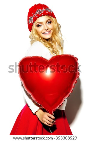 portrait of beautiful happy sweet cute smiling blonde woman girl in casual hipster clothes, in pink skirt and winter warm beanie with red heart balloon in hands - stock photo
