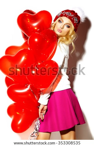 portrait of beautiful happy sweet cute smiling blonde woman girl in casual hipster clothes, in pink skirt and winter warm beanie with red heart balloons in hands gives air kiss - stock photo