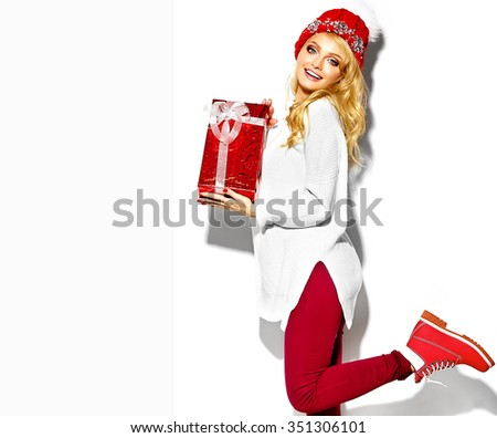 portrait of beautiful happy sweet smiling blonde woman girl holding in her hands big Christmas gift box in casual red hipster winter clothes, in white warm sweater standing on one leg - stock photo