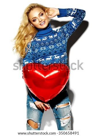 portrait of beautiful happy sweet smiling blonde woman girl holding in her hands big red heart balloon in casual hipster warm winter clothes, in blue sweater  - stock photo