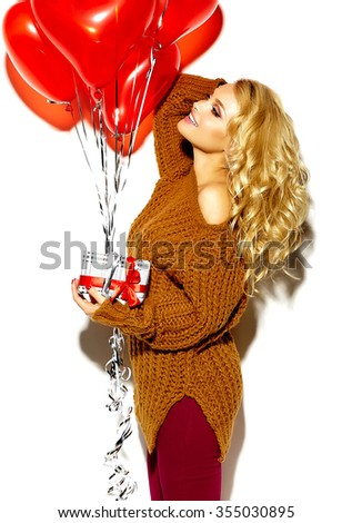 portrait of beautiful happy sweet smiling blonde woman girl holding in her hands Christmas gift box and heart balloons in casual red hipster winter clothes, in brown warm sweater  - stock photo