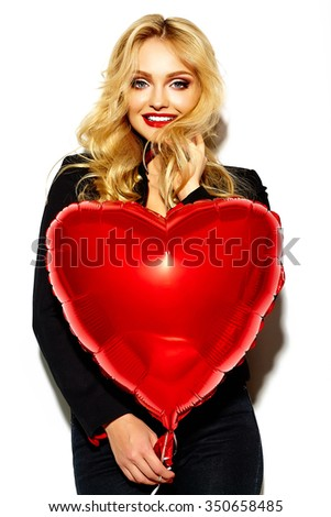 portrait of beautiful happy sweet smiling blonde woman girl holding in her hands red heart balloon in casual black hipster clothes - stock photo