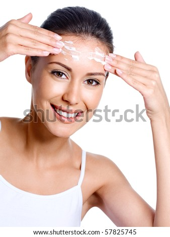 Portrait of beautiful happy woman applying cream on her forehead - white background - stock photo