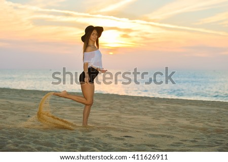 Portrait of beautiful happy woman in hat and shorts enjoying sunset beach background outside - stock photo