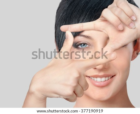 Portrait of beautiful happy woman making frame with fingers - stock photo