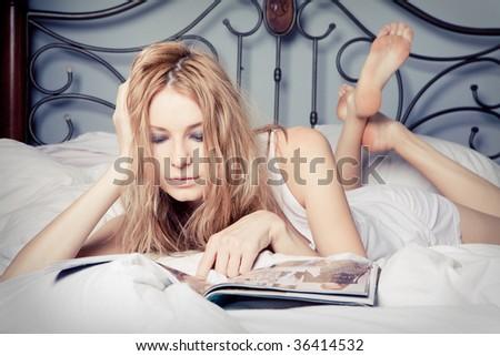 Portrait of beautiful happy woman reading magazine at bedroom - stock photo
