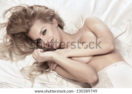 Portrait of beautiful happy young girl lying in bed covering her breast. Long curly blonde hair, amazing makeup. - stock photo