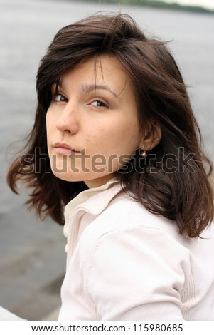 Portrait of beautiful haughty woman with disorder hair on water background.