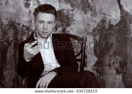 Portrait of beautiful imposing man on vintage wall background. Sits on vintage chair and looking at cell phone. Blond. Dressed in classic formal suit. Vintage Black and White colour graded.