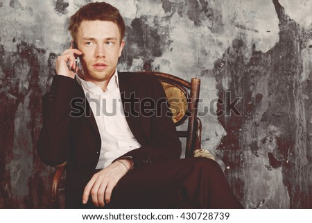 Portrait of beautiful imposing man on vintage wall background. Sits on vintage chair and talking on mobile phone. Blond. Dressed in classic formal suit. Oldshool 70s colour graded.