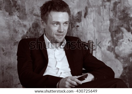 Portrait of beautiful imposing man on vintage wall background. Sits on vintage chair with  cell phone. Blond. Dressed in classic formal suit. Vintage Black and White colour graded.