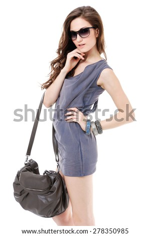Portrait of beautiful in sunglasses with bag posing on white background - stock photo