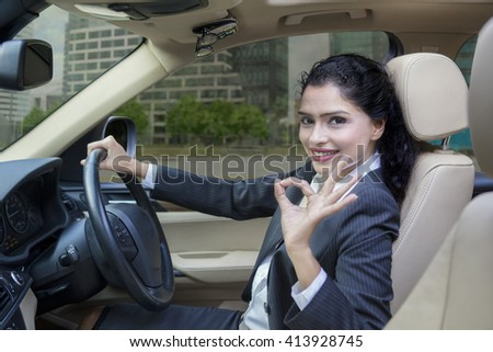Portrait of beautiful Indian businesswoman driving a new car on the road while showing OK sign - stock photo