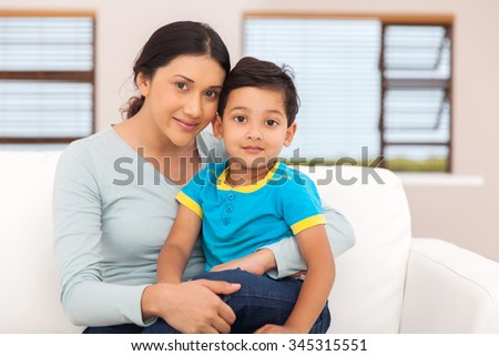 portrait of beautiful indian mother and little boy sitting at home - stock photo