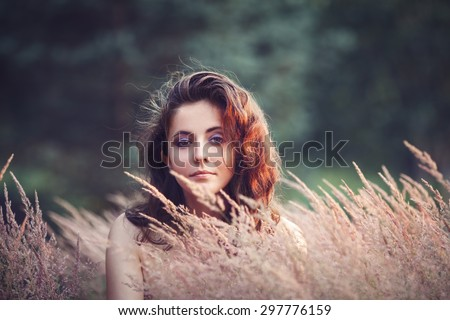 Portrait of beautiful  innocent Caucasian adult girl woman with long dark red brown hair, hazel eyes in park field outside on sunset in golden hour looking in camera - stock photo