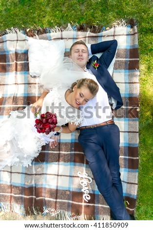Portrait of beautiful just married couple relaxing on green grass at park - stock photo