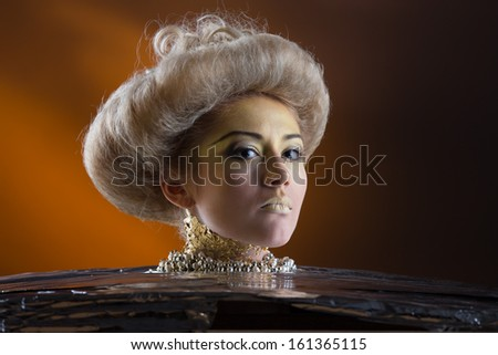 Portrait of Beautiful lady with voluminous hair style and bright make up in gold colors