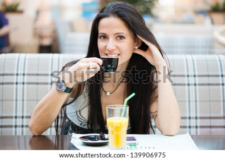 Portrait of beautiful latin woman drinking coffee in cafe - stock photo