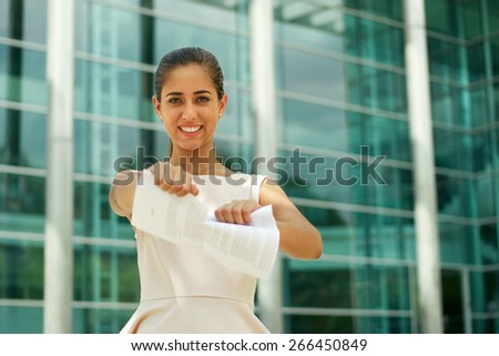 Portrait of beautiful latina businesswoman resigns from job, tearing a employment contract and looking happy at camera, smiling and holding the document.  - stock photo