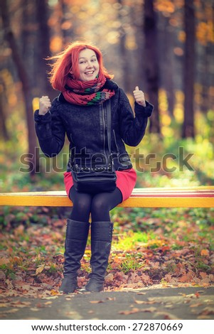 Portrait of beautiful laughing red-haired woman sitting on bench in autumn park (shallow dof) - stock photo