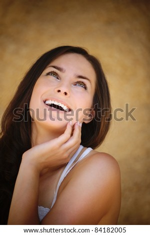 Portrait of beautiful laughing young brunette woman propping up her face and looking up against beige background.