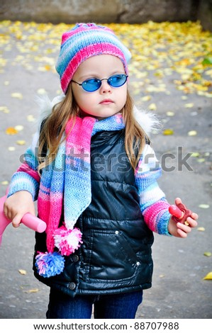 Portrait of beautiful little blond girl in glasses outside - stock photo