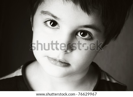 Portrait of beautiful little boy with attentive look, studio shot, vintage style - stock photo