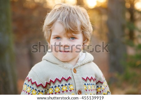 Portrait of beautiful little caucasian boy of 2 , outdoors. Evening light. Kid byo smiling and looking at the camera. With blond hairs and blue eyes, happy child. - stock photo