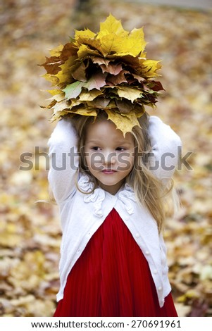 Portrait of beautiful little girl, against background of autumn park - stock photo