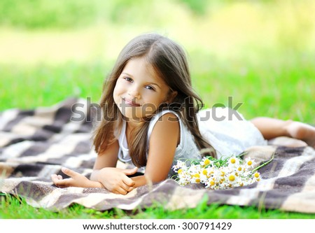 Portrait of beautiful little girl child with chamomiles flowers lying on the plaid outdoors - stock photo