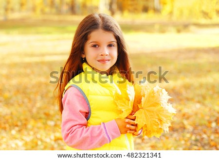Portrait of beautiful little girl child with yellow maple leafs in autumn day