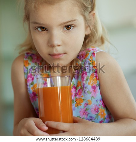 Portrait of beautiful little girl close-up, which sits on table and drinking juice from glass. - stock photo